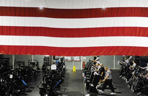 A large American flag hangs above a large room. It's full of exercise bikes, treadmills, and the usual execise equipment.