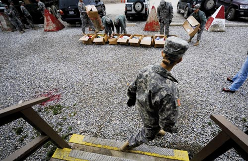 Shipping boxes are lined up in a gravel yard, where several soldiers look through the contents.