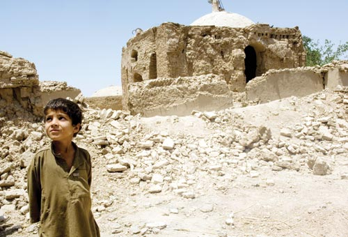 A young boy, wearing a brown galabiyya, stands in front of a pile of rock rubble, behind which are the badly-damaged remains of a simple mosque.