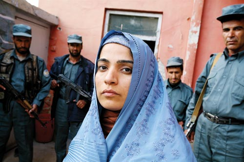 Clad in a sky-blue hijab, a young woman is flanked by four armed men.