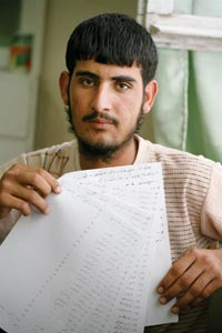 A young man holds up several hand-written pages.