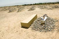 A simple coffin lies next to a grave. The grave is one of dozens. Each one consists of a pile of stones, with one large, upright headstone.