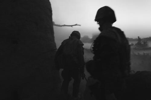In near-dark, two soldiers move through thick air.
