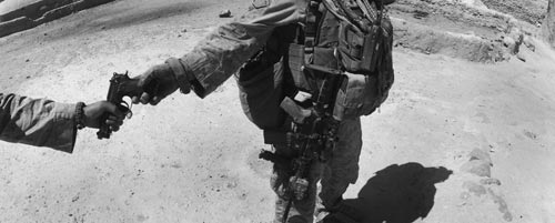 A soldier swathed with gear passes a handgun to another man.