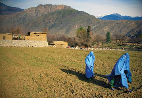 A trio of women, clad in sky-blue burqas, walk across a muddy field. Tall, rugged mountains rise behind them.