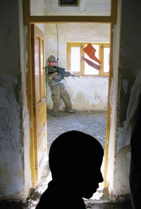 A camouflaged soldier stands in the corner of a white-and-yellow classrom. In the foreground, a boy's head is silhouetted.