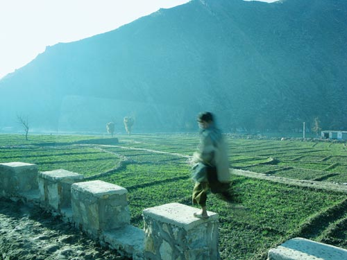 In bright morning light, a boy jumps between stone pillars that line a road. Behind him is a green field, over which an enormous mountain looms.