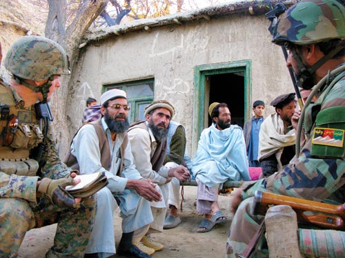 Solders and Afghani men sit on benches under a tree. Behind them is a low building, with some boys standing in front of it.