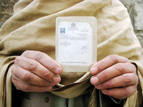 A man displays for the camera a crudely-fashioned identification card, about the size of a passport. It consists of an irregularly shaped piece of paper sealed in translucent laminate.