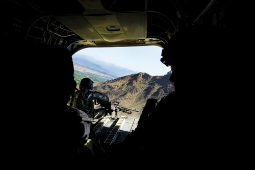 Within an unlit helicopter, we see out of the large, open door. Outside, below, is a craggy, brown mountain and, beyond that, a green valley, and then more mountains. Perched at the edge of the door is a soldier manning a large rifle that's mounted on the floor of the helicopter.