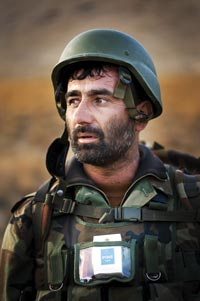 A bearded soldier looks at something off-camera. He wears a helmet, though doesn't have it affixed to his head. In a pocket on the front of his uniform can be seen a pack of cigarettes and a lighter.