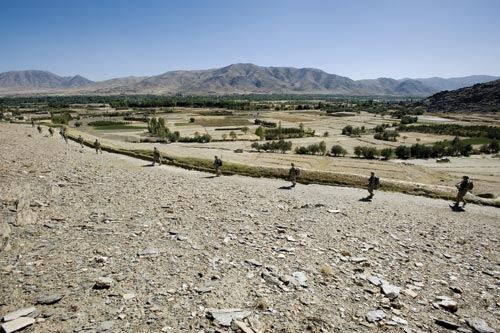 A line of soldiers stretches across a desolate, rock-strewn valley floor. Each is separated by perhaps fifteen feet. Behind them, mountains rise into the air.