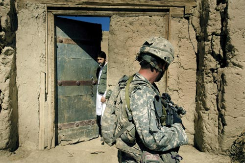 A casually-dressed man stands at a partially-opened, large, wood-and-bronze door in a cracked and ancient-looking wall. Perhaps twenty feet away from the door is an American soldier, rifle at the ready. They appear to pause, looking at each other.