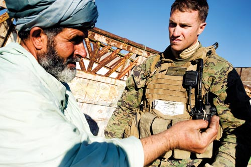 A turbaned, middle-aged man gesticulates while talking to a young soldier. The soldier has taken his helmet off, and squints against the sun as he looks at the man.