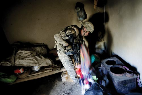 In an unlit, cluttered, dirty-looking room, an American soldier digs through a pile on the floor.