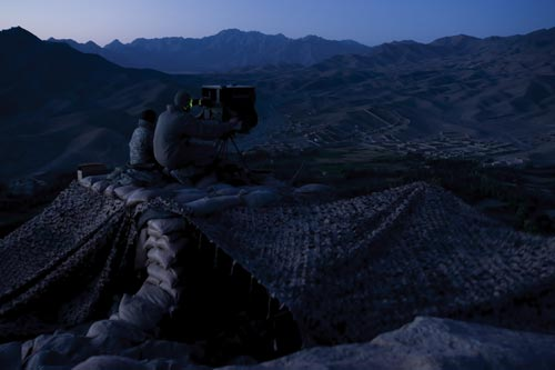 Perched on a mountaintop at dusk, two men peer into a large, tripod-mounted box. Around them are sandbags and camouflaged netting. Below them, in the distance, can be seen a settlement in a valley. The are surrounded by great mountains, and in the dying light they look like soft folds of fabric.