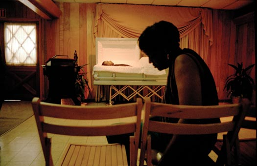 In the background, half of a casket is open, displaying the body within. In the foreground, a black-clad woman sits on a folding chair. The room has a tile floor, light-colored wood walls, and a drop ceiling.