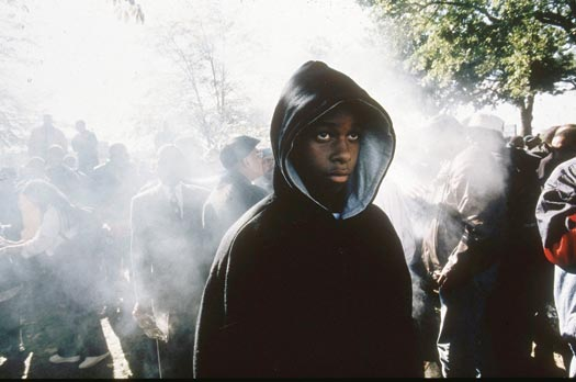 Standing alone in a gathering of people outdoors, a teenaged boy wears a black, hooded sweatshirt, the hood up over his head. He looks straight ahead and up a little, with an intensity to his gaze. Behind him, the crowd is obscured by what appears to be smoke.