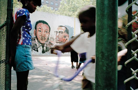 Children play on a paved playground adjacaent to a brick public housing complex. Behind them is a wall with a mural with large depictions of Martin Luther King Jr. and Malcolm X, partially covered with grafitti.