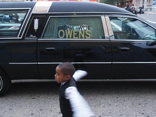 A formally dressed young boy plays while standing a few feet away from a Hearse.
