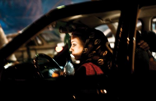 A young woman sits behind the wheel of a darkened car. Her headscarf has slipped back, uncovering most of her head. She holds a bottle of water in one hand. A passenger is in the car as well.