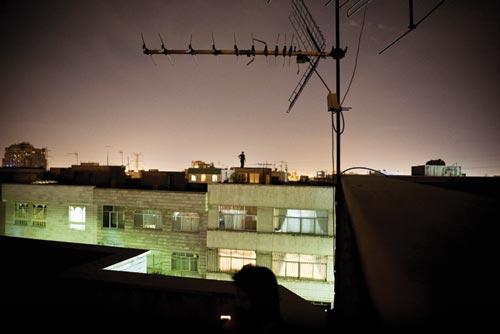 From one rooftop, the rooftop of an adjacent building can be seen. Silhouetted against the glow of city lights at night is the figure of a lone man, one hand on his hip.