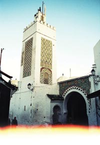 A four-sided minaret rises several stories above the whitewashed walls of a mosque.