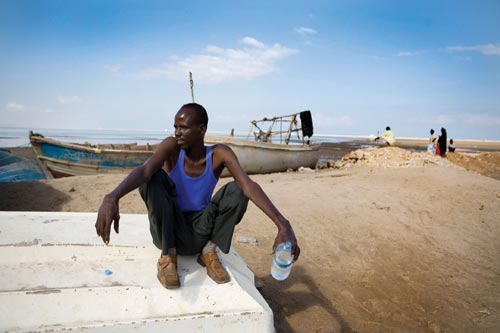A young man squats on an overturned boat, a bottle of water in his hand. He's wearing a blue sleeveless t-shirt and a worn-looking pair of dress shoes. Behind him can be seen a few other small boats and a few people looking out at the sea.
