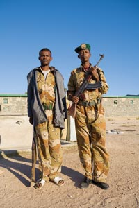 Two young soldiers pose for the camera. Both are wearing oversized desert-style camouflage. One has a green beret, an automatic weapon with a banana clip, and black dress shoes. The other is hatless, wears a gray windbreaker and white sandals, and carries an ancient-looking rifle.
