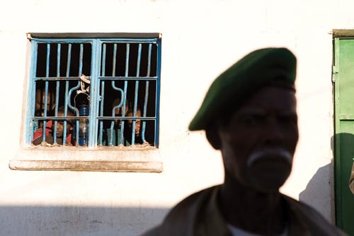 In the background, four men cluster around a heavily barred window to which a lantern is tied. In the foreground, blurred, a dubious-looking mustached man looks at the camera, a green beret perched on his head.