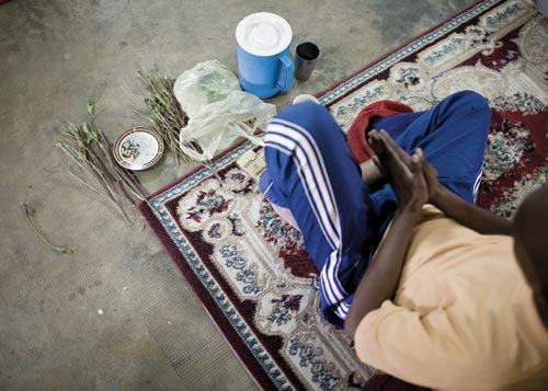 A young man sits on a woven rug, hands clapsed together as if in prayer. Laid out before him are a pack of cigarettes, a bunch of dried plants, a pitcher, and a cup.