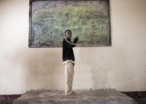 A boy, clad in khakis and a sweater, stands in front of a chalkboard, chalk in hand.
