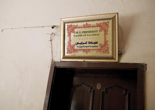 "A certificate hangs on a cracked wall above a door, surrounded by exposed wiring. It reads ""H.E.PRESIDENT,"" and ""Republic OF Samalialand."""