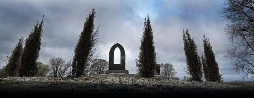 Gray winter skies loom over the prominence of a monument. It's surrounded by tall, thin evergreens. The ground is covered with hand-sized stones.