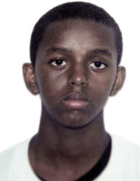 An official-looking portrait of a boy, looking perhaps old enough to be in high school. His hair is close-cropped and his ears stick out. He wears a white T-shirt. He does not smile.