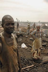Bedraggled figures dot a smoky landscape. In the foreground stands a man, eyes closed, wearing a soot-stained steeleveless t-shirt. Behind him stands a woman, hands on her hips, wearing sandals and drab-colored clothes. A small pile of chunks of wood is on the ground between them. Smoke rises here and there.