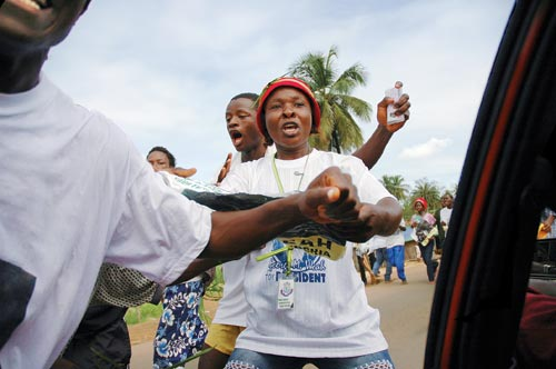 "A sparse crowd, marching down the street, addresses their chants to the photographer, who is inside of a car. The woman at the center of the frame has her mouth open, speaking. She wears a ""George M. Weah for PRESIDENT"" T-shirt and jeans."