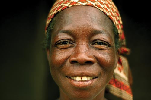 A portrait of a middle-aged woman. She looks directly at the camera, smiling. There is a gap between her front teeth. Below her headscarf can be seen a tangle of graying black hair. The skin around her eyes crinkles up.