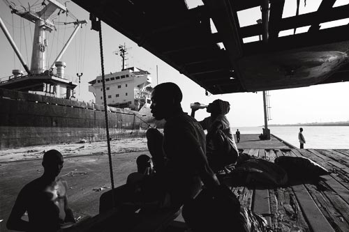 Several men rest in a patch of shade on a pier. Behind them looms a large factory trawler.
