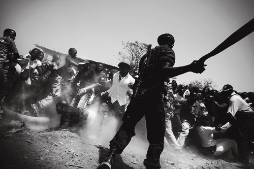 A menacing-looking soldier swings a machete to clear a crowd. Dozens of people have jumped back or dived for the ground to escape the blade, raising a cloud of dust.