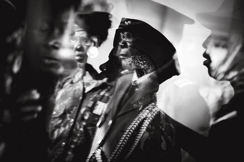 Decorated middle-aged soldiers, standing at attention, photographed in a double exposure.