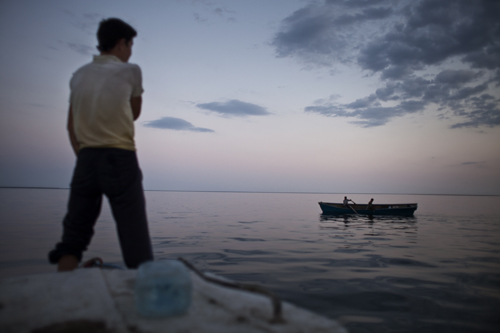 Fishermen from Tactubek cast their nets at dusk on the Aral Sea.