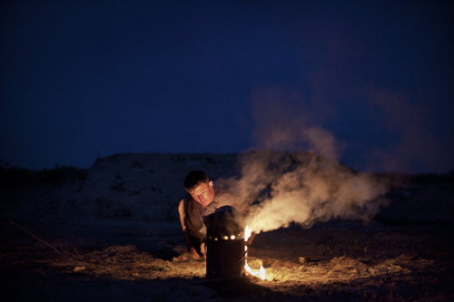 Nyrbek cooks dinner for himself and his brother Islam over an outdoor fire pit at night on a deserted piece of land.