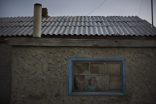 Six-year-old Daylet Ayaganov looks out the window of one of only twenty houses in Tactubek.