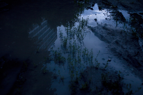 The moon is reflected in a puddle outside the locked-up Electron-Gaz plant in Zholtiy Vodi, Ukraine.