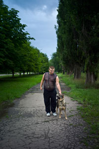Oleg, a Zholtiy Vodi resident, walks his dog Kira down the cracked sidewalk across the street from the Electron-Gaz plant.