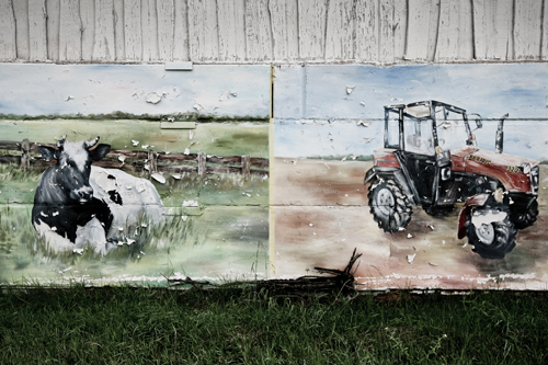 A mural tribute to the tractor, paint flecking from age.