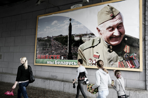 Pedestrians pass a billboard honoring Soviet-era war veterans in downtown Minsk.
