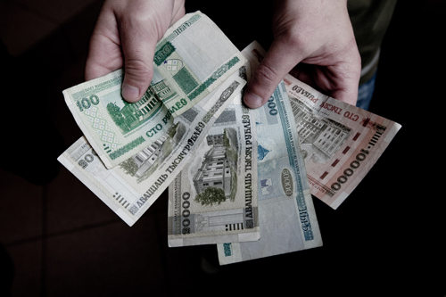 "Hands holding Russian currency, newly printed prior to the elections to support Lukashenko's proposed ""salary hike""."
