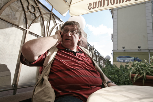 Alexander Feduta takes a phone call and warily scans the patrons of a street-side cafe in Minsk.